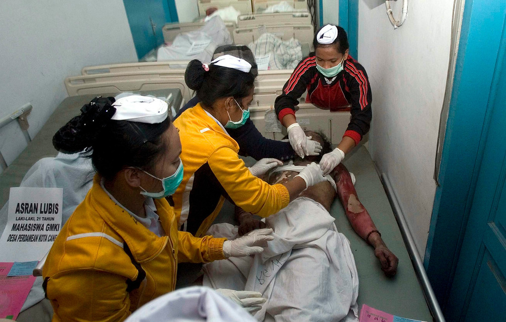 . Indonesian paramedics clean up a body of the Sinabung volcanic eruption victim at a hospital in Kabanjahe, Karo, North Sumatra, Indonesia, 01 February 2014. At least 14 people were killed when a volcano on the Indonesian island of Sumatra spewed lava and hot gas, an aid worker said. The eruption of Mount Sinabung came a day after the National Disaster Management Agency said residents living farther than five kilometres from the peak were being allowed to return to their homes after a lull in activity.  EPA/DEDI SAHPUTRA