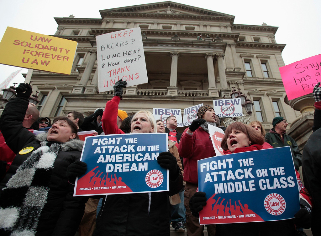 """. Anti right-to-work protesters yell outside of Michigan\'s state capitol building in Lansing December 11, 2012. The Republican-majority Michigan legislature gave final approval on Tuesday to \""""right-to-work\"""" restrictions on public sector unions in a state considered a stronghold of organized labor, as protesters chanted in the gallery and thousands rallied outside.  REUTERS/Rebecca Cook"""
