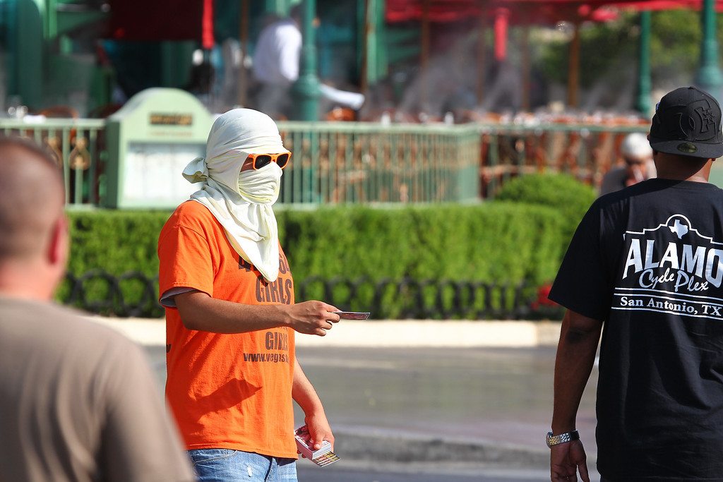 . A man hands out advertisements for adult entertainment during a heat wave on the Las Vegas Strip on Sunday, June 30, 2013.  (AP Photo/Las Vegas Review-Journal, Chase Stevens)