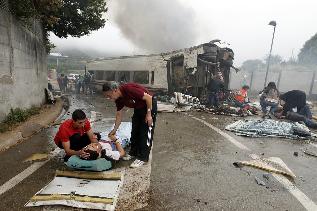 . A picture taken on July 24, 2013 shows two men comforting an injured woman next to a derailed car following a train accident near the city of Santiago de Compostela.  AFP PHOTO / LA VOZ DE GALICIA / XOAN A. SOLER / MONICA FERREIROSXOAN A. SOLER,MONICA FERREIROS/AFP/Getty Images