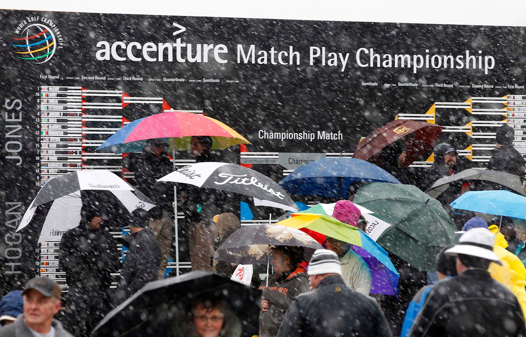 . Snow falls on golf fans at they look for cover during the first round of the WGC-Accenture Match Play Championship golf tournament in Marana, Arizona February 20, 2013. REUTERS/Matt Sullivan