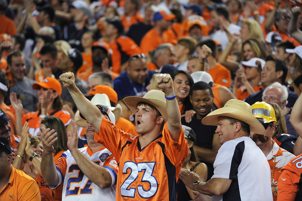 . Broncos fans celebrate a touchdown in the second quarter. The Denver Broncos took on the Baltimore Ravens in the first game of the 2013 season at Sports Authority Field at Mile High in Denver on September 5, 2013. (Photo by Tim Rasmussen/The Denver Post)