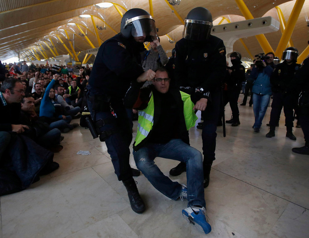 . An Iberia worker is removed by Spanish riot police officers during clashes at Terminal 4 of Madrid\'s Barajas airport February 18, 2013. Workers at loss-making Spanish flag carrier Iberia began a five-day strike at midnight on Monday, grounding over 1,000 flights and costing the airline and struggling national economy millions of euros. REUTERS/Sergio Perez