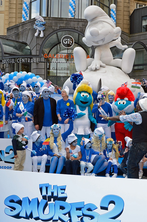 . Smurf Ambassadors pose for a group photo below a Smurf sculpture in front of the Brussels Central railway station as part as Global Smurfs Day celebrations on June 22, 2013 in Brussels, Belgium.  (Photo by Pascal Le Segretain/Getty Images for Sony Pictures Entertainment)
