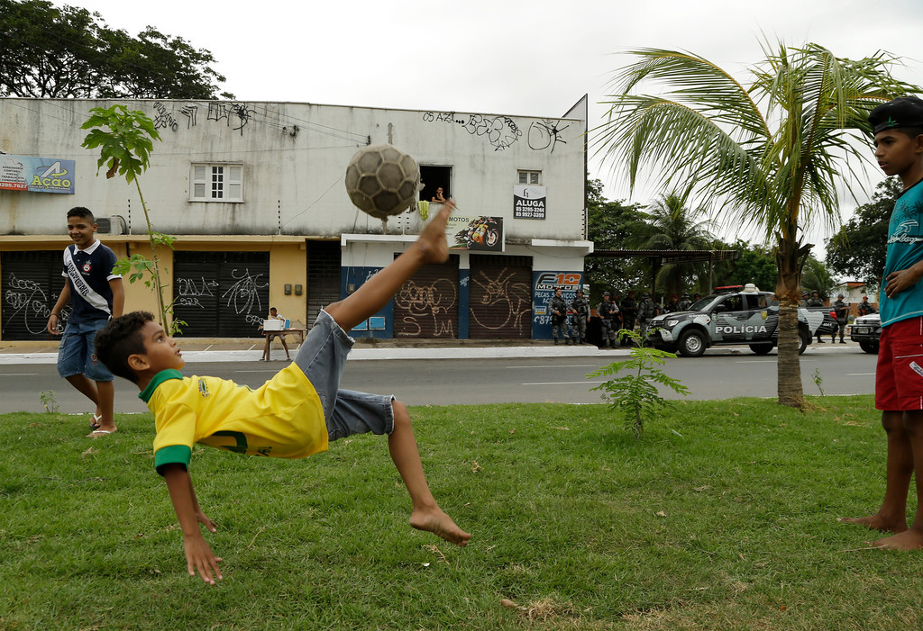 . A boy performs a bicycle kick on a street in Fortaleza prior to the group A World Cup soccer match between Brazil and Mexico at the Arena Castelao in Fortaleza, Brazil, Tuesday, June 17, 2014.  (AP Photo/Themba Hadebe)