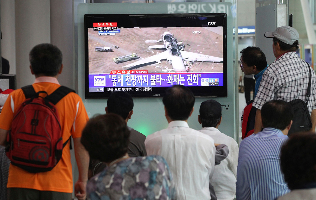 """. People watch a news program reporting about Asiana Airlines flight 214 which took off from Seoul and crashed while landing at San Francisco International Airport, at Seoul Railway Station in Seoul, South Korea, Sunday, July 7, 2013. The writing on the screen reads \"""" Fire on the ceiling of the airplane.\"""" (AP Photo/Ahn Young-joon)"""