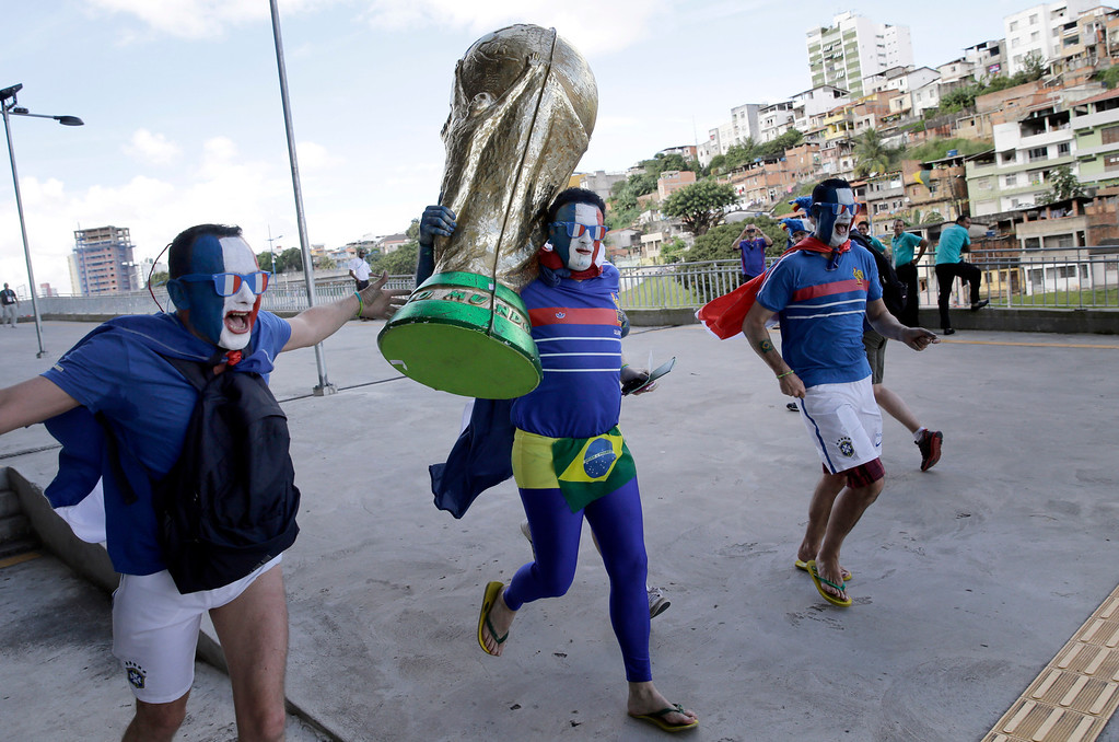. French soccer fans in costume run with a large replica of the World Cup trophy as they arrive to Arena Fonte Nova for their team\'s World Cup match with Switzerland in Salvador, Brazil, Friday, June 20, 2014. (AP Photo/Christophe Ena)
