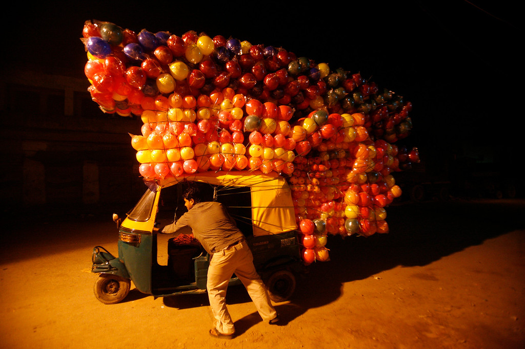 . A man pushes an auto-rickshaw loaded with plastic balls to sell at a wholesale market in New Delhi November 10, 2011. REUTERS/Parivartan Sharma