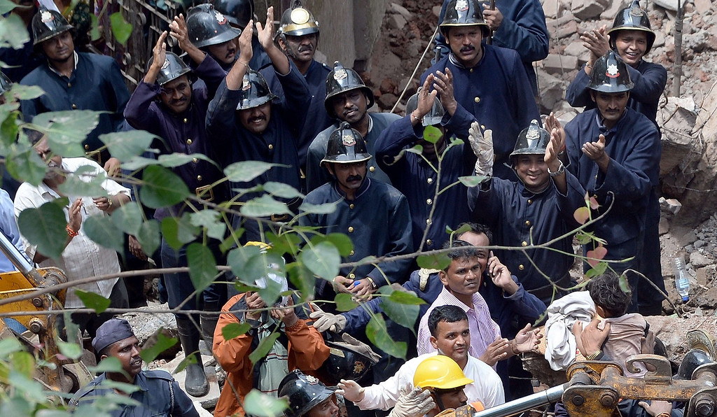. Firefighters applaud as a child (bottom R) is brought out alive from the rubble of a building collapse in Mumbai on September 27, 2013.   AFP PHOTO/Indranil MUKHERJEE/AFP/Getty Images