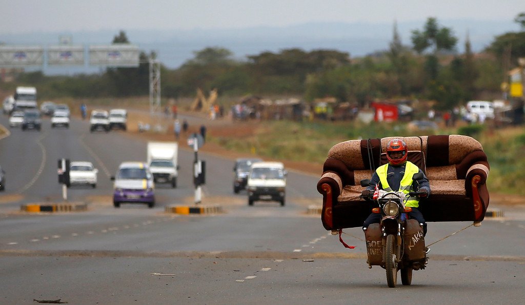 . A man carries a sofa on his motorcycle on a highway near Kenya\'s capital Nairobi March 10, 2013.  REUTERS/Marko Djurica