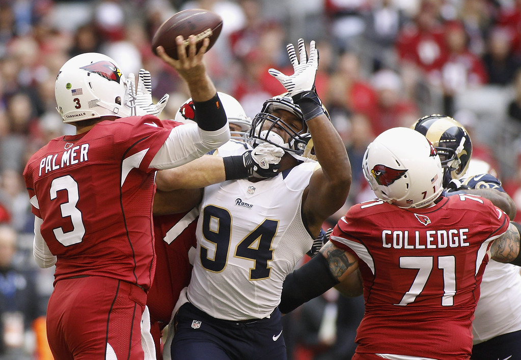 . Defensive end Robert Quinn #94 of the St Louis Rams pressures quarterback Carson Palmer #3 of the Arizona Cardinals as he throws a pass during the first quarter of their NFL football game at University of Phoenix Stadium on December 8, 2013 in Glendale, Arizona.  (Photo by Ralph Freso/Getty Images)