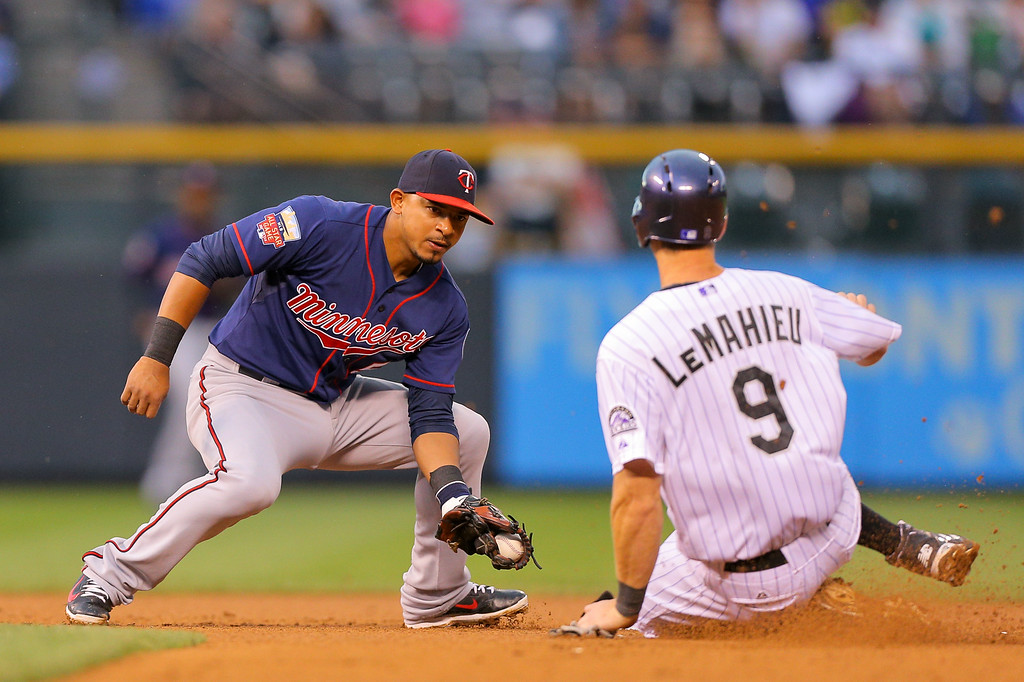 . DENVER, CO - JULY 11: Shortstop Eduardo Escobar #5 of the Minnesota Twins applies the tag as DJ LeMahieu #9 of the Colorado Rockies is caught stealing during the fourth inning at Coors Field on July 11, 2014 in Denver, Colorado. (Photo by Justin Edmonds/Getty Images)