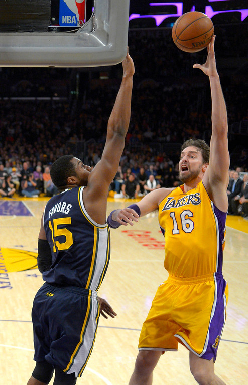 . Los Angeles Lakers center Pau Gasol, right, of Spain, puts up a shot as Utah Jazz forward Derrick Favors defends during the first half of an NBA basketball game, Friday, Jan. 3, 2014, in Los Angeles. (AP Photo/Mark J. Terrill)