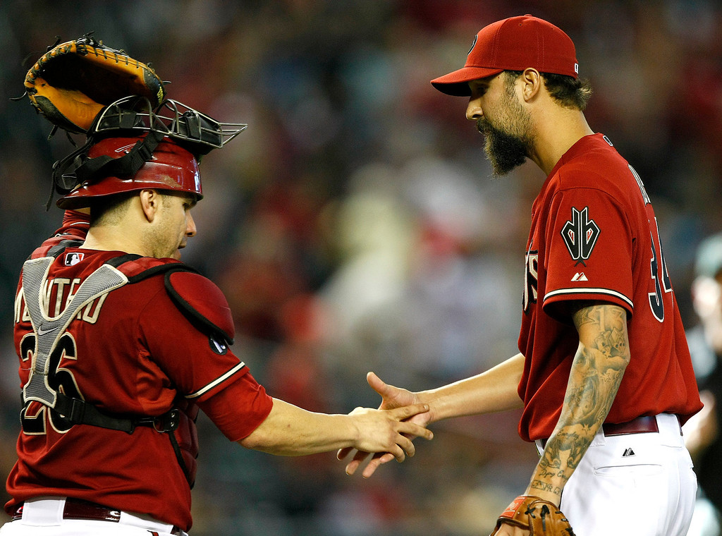 . Arizona Diamondbacks catcher Miguel Montero, left, celebrates with teammate Chaz Roe, right, after defeating the Colorado Rockies 8-2 in 2a baseball game on Sunday, Sept. 15, 2013, in Phoenix. (AP Photo/Rick Scuteri)