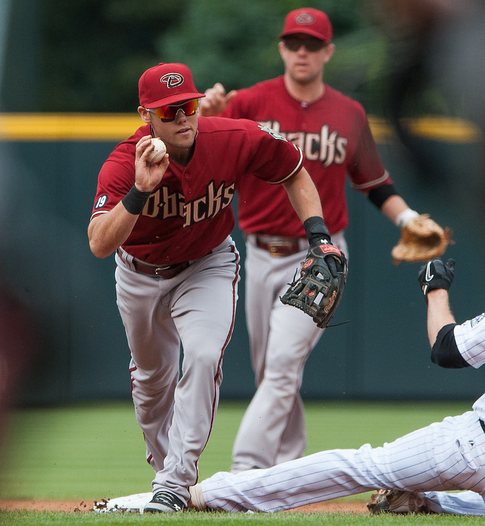 . Chris Owings #16 of the Arizona Diamondbacks shows possession of the ball to the umpire after forcing out a runner at second base in the first inning of a game against the Colorado Rockies at Coors Field on September 22, 2013 in Denver, Colorado.  (Photo by Dustin Bradford/Getty Images)