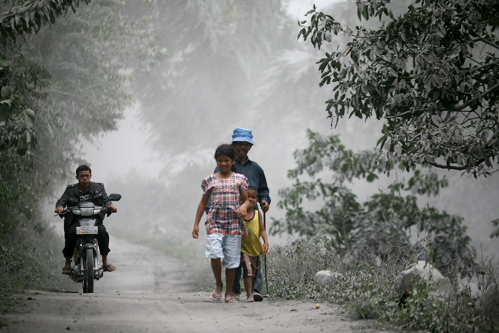 . Villagers walk on a road covered with volcanic ash from Mount Sinabung\'s eruption in Mardingding, North Sumatra, Indonesia, Monday, Nov. 4, 2013.  The volcano erupted Sunday, unleashing volcanic ash high into the sky and forcing the evacuation of villagers living around its slope. (AP Photo/Binsar Bakkara)