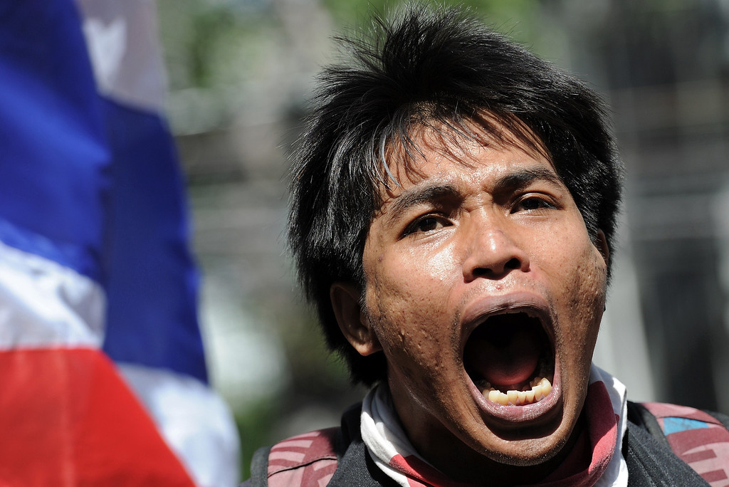 . A Thai opposition protester shouts slogans as protesters face off with police deployed to guard the ruling Puea Thai party headquarters in Bangkok on November 29, 2013. Defiant Thai opposition protesters stormed the army headquarters and besieged Prime Minister Yingluck Shinawatra\'s party offices on November 29, intensifying their fight to bring down her government. AFP PHOTO / Christophe ARCHAMBAULT/AFP/Getty Images