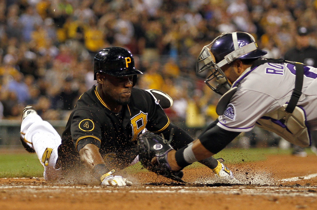 . PITTSBURGH, PA - JULY 18:  Wilin Rosario #20 of the Colorado Rockies tags out Starling Marte #6 of the Pittsburgh Pirates in the sixth inning during the game at PNC Park July 18, 2014 in Pittsburgh, Pennsylvania.  (Photo by Justin K. Aller/Getty Images)