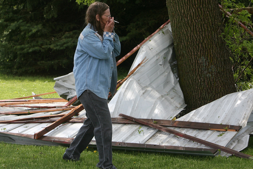 . June McFarland reacts to the first sight of storm damage in rural Osage, Iowa on Sunday, May 19, 2013. A powerful weather system moved through the area on Sunday afternoon triggering tornado warnings, high winds and hail. (AP Photo/The Globe Gazette, Arian Schuessler)