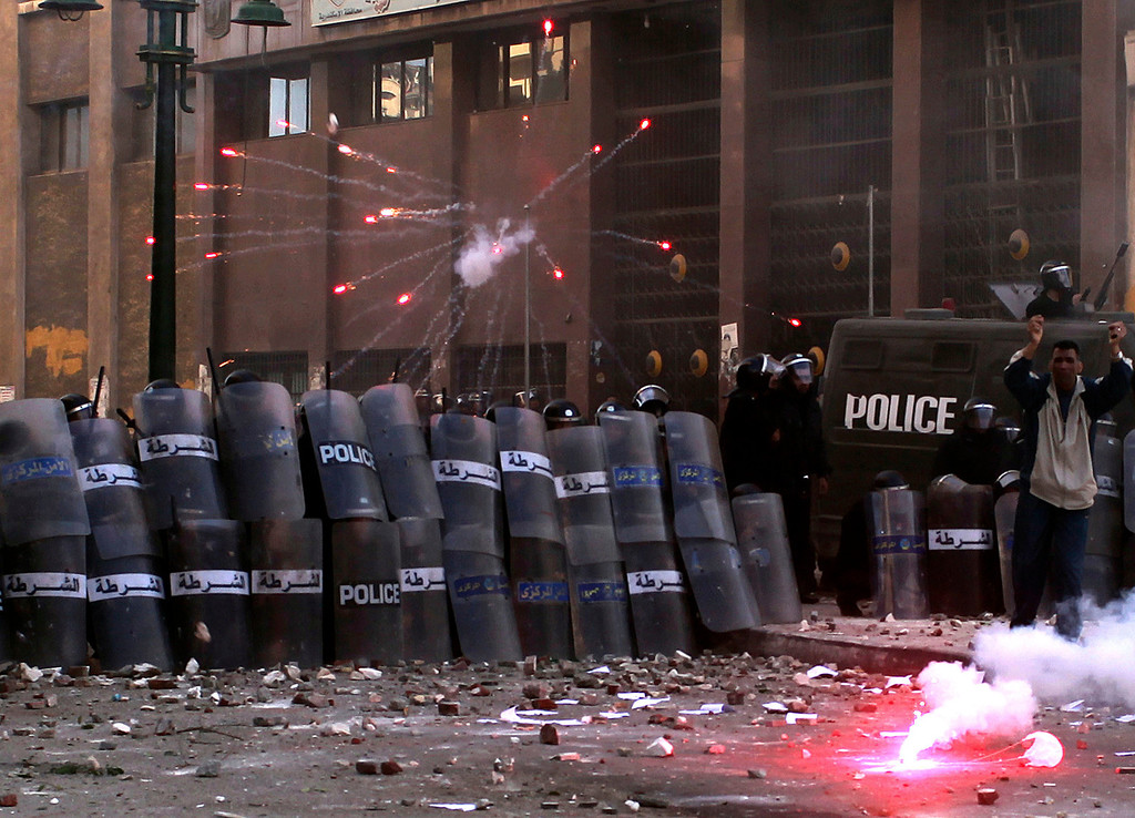 . Riot police take cover as protesters throw flares and stones during clashes in Alexandria January 25, 2013. Youths fought Egyptian police in Cairo and Alexandria on Friday on the second anniversary of the revolt that toppled Hosni Mubarak and brought the election of an Islamist president who protesters accuse of riding roughshod over the new democracy.  REUTERS/Asmaa Waguih
