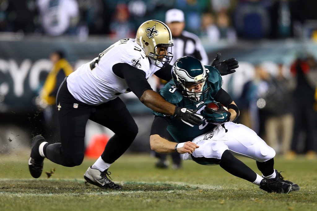 . PHILADELPHIA, PA - JANUARY 04:   Cameron Jordan #94 of the New Orleans Saints tackles Nick Foles #9 of the Philadelphia Eagles during their NFC Wild Card Playoff game at Lincoln Financial Field on January 4, 2014 in Philadelphia, Pennsylvania.  (Photo by Elsa/Getty Images)