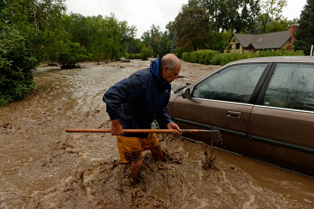 . BOULDER, CO - SEPTEMBER 12: Cenobio Chacon tries to get his sons car out of the path of the flood outside his home in north Boulder, September 12, 2013. The car is stuck in the middle of Topaz Dr. that is covering in running flood water. Massive flash flooding is on going along the Front Range of Colorado. (Photo By RJ Sangosti/The Denver Post)
