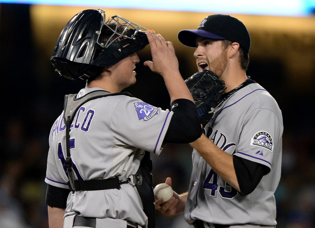 . LOS ANGELES, CA - SEPTEMBER 27:  Collin McHugh #43 and Jordan Pacheco #15 of the Colorado Rockies react after a two run double to Juan Uribe #5 of the Los Angeles Dodgers during the first inning at Dodger Stadium on September 27, 2013 in Los Angeles, California.  (Photo by Harry How/Getty Images)