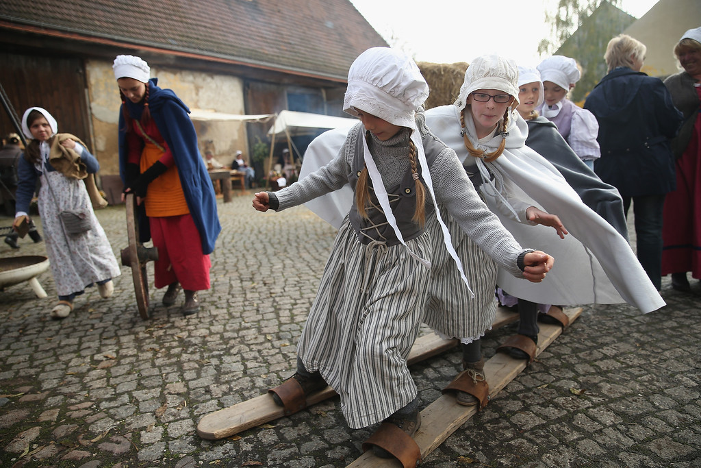 . Local children dressed in early-19th century regional period clothing play games in a recreated 1813 village in Liebertwolkwitz district during events to commemorate the 200th anniversary of The Battle of Nations on October 16, 2013 in Leipzig, Germany.  (Photo by Sean Gallup/Getty Images)