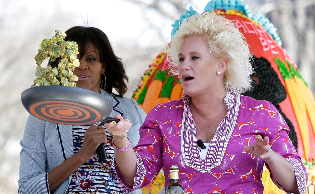 . U.S. first lady Michelle Obama (L) cooks with television chef Anne Burrell (R) at the healthy eating station during the Easter Egg Roll on the South Lawn of the White House in Washington, April 1, 2013. REUTERS/Jonathan Ernst