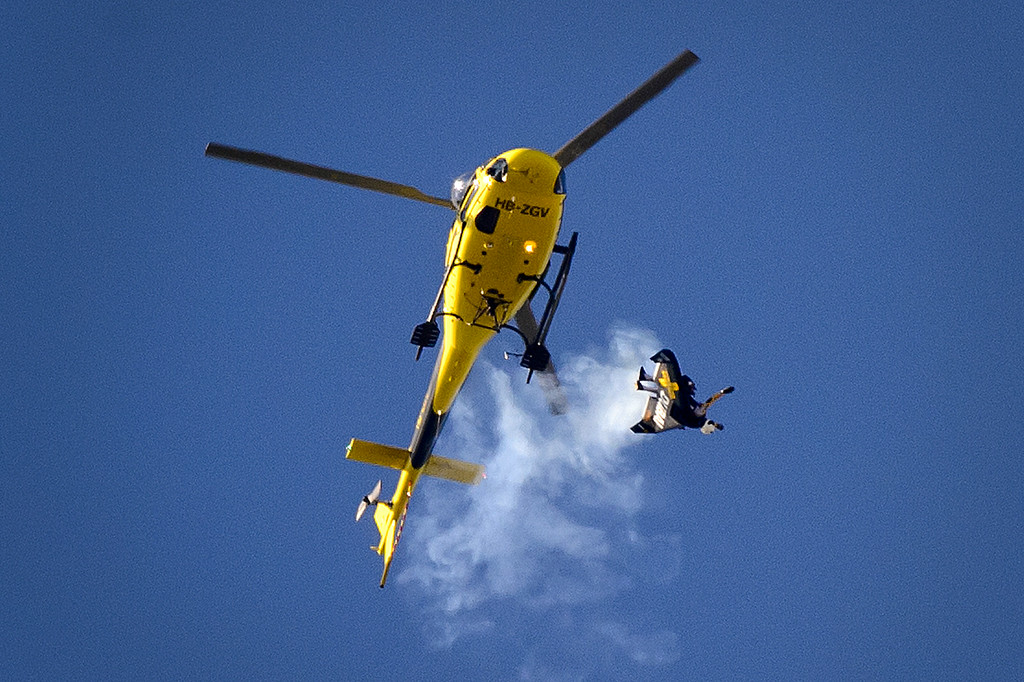 """. Swiss pilot Yves Rossy known as the \""""Jetman\"""" jumps from a helicopter with his jet-powered two meters wingspan wing attached to his back during the first day of AIR14 air show on August 30, 2014 in Payerne, western Switzerland. AFP PHOTO / FABRICE COFFRINI/AFP/Getty Images"""