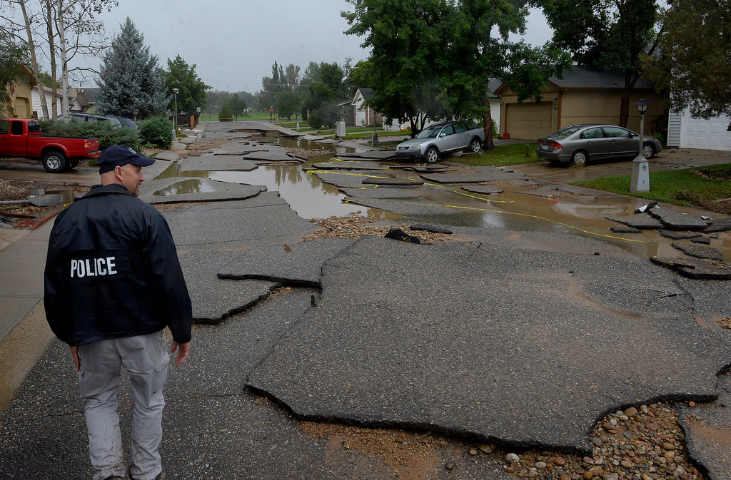 . LONGMONT, CO. - SEPTEMBER 15: Detective Ed Tinkum looks over Hayden Court which collapsed during the flooding of theTroxell neighborhood in Longmont,  CO September 15, 2013.  Evacuations are underway Sunday morning in some Longmont neighborhoods because the St. Vrain River is rising quickly. (Photo By Craig F. Walker / The Denver Post)