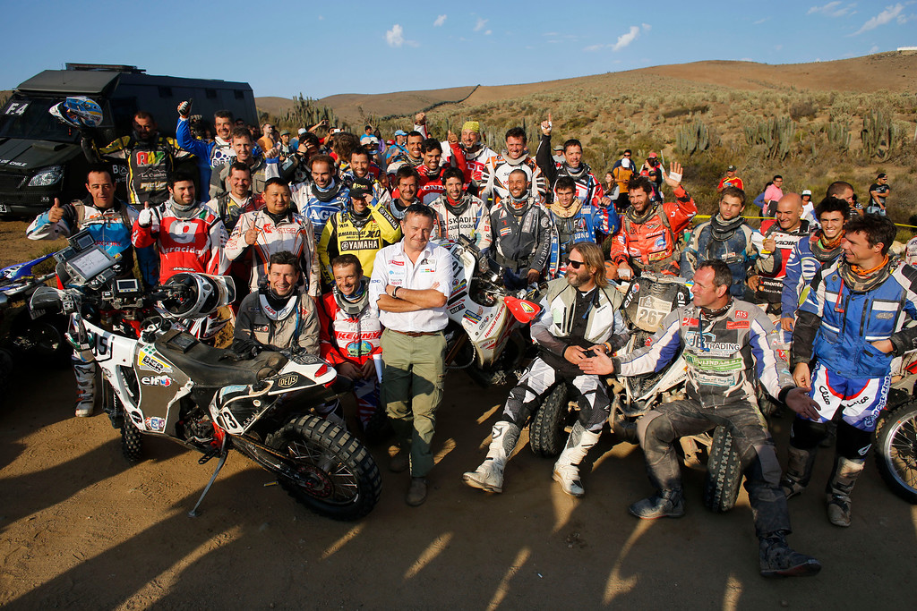 . Dakar Rally Director Etienne Lavigne, center in white shirt, poses with motorcycle riders at the start of the special of the thirteenth stage of the Dakar Rally between the cities of La Serena and Valparaiso, Chile, Saturday, Jan. 18, 2014. (AP Photo/Victor R. Caivano)
