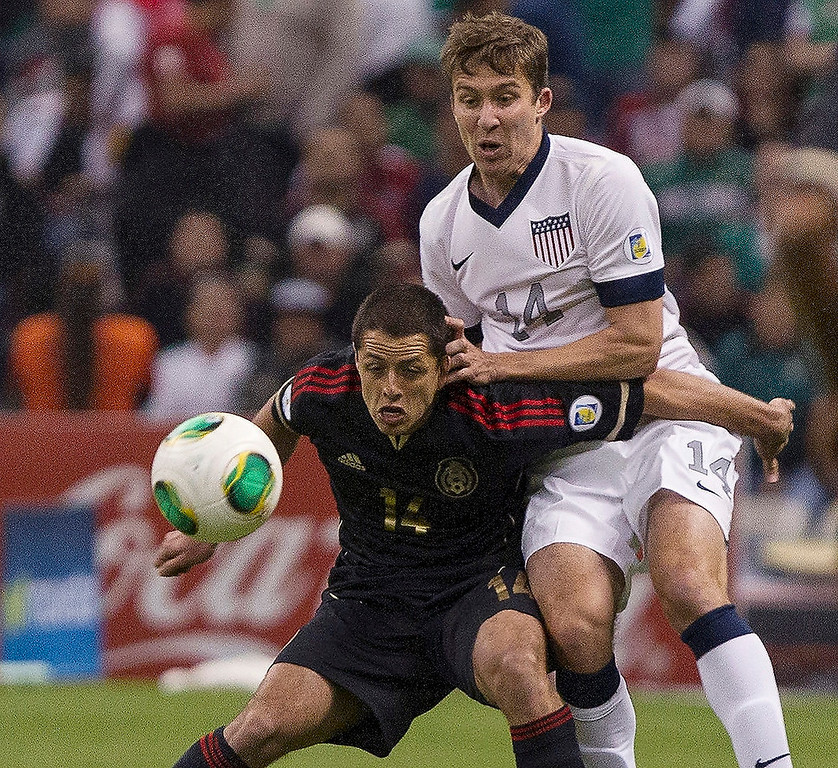 . Javier Hernandez (#14) of Mexico fights for the ball with Mattew Besler (#14) of the United States during a match between Mexico and US as part of FIFA 2014 World Cup Qualifier at The Azteca stadium on March 26, 2013 in Mexico City, Mexico. (Photo by Miguel Tovar/Getty Images)