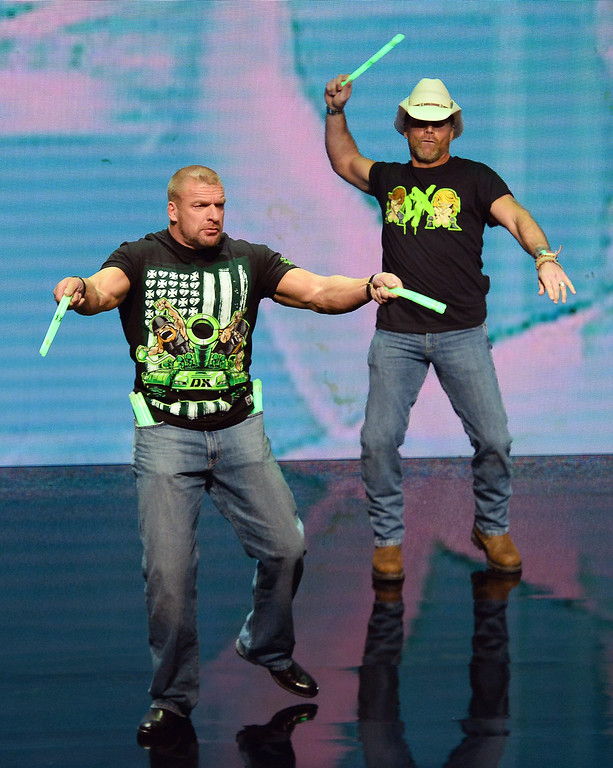 . WWE personalities Triple H (L) and Shawn Michaels throw glow sticks into the crowd at a news conference announcing the WWE Network at the 2014 International CES at the Encore Theater at Wynn Las Vegas on January 8, 2014 in Las Vegas, Nevada. The network will launch on February 24, 2014 as the first-ever 24/7 streaming network, offering both scheduled programs and video on demand. The USD 9.99 per month subscription will include access to all 12 live WWE pay-per-view events each year. CES, the world\'s largest annual consumer technology trade show, runs through January 10 and is expected to feature 3,200 exhibitors showing off their latest products and services to about 150,000 attendees.  (Photo by Ethan Miller/Getty Images)