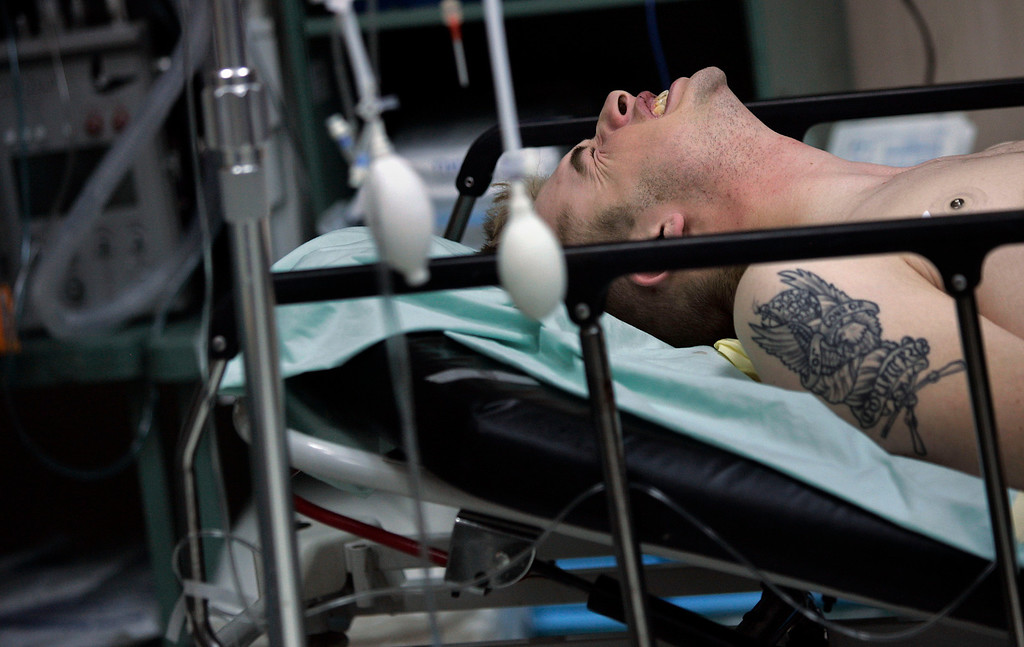 . A U.S. soldier in the 10th Mountain Division winces in pain as his gunshot wound to the leg is treated by medics of the  28th Combat Support Hospital based in Ft. Bragg, North Carolina February 27, 2007 in Baghdad, Iraq. Wounded children and adults were rushed to the 28th Combat Support Hospital in Baghdad, a military hospital that took wounded Iraqi and U.S. forces alike. The soldier had shrapnel wounds and a piece of shrapnel lodged in his skull but is expected to recover.  (Photo by Chris Hondros/Getty Images)