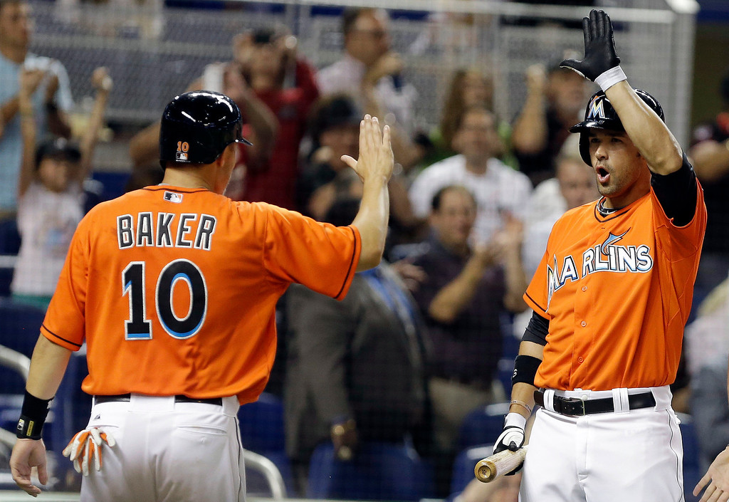 . Miami Marlins\' Jeff Baker (10) is met by Garrett Jones after scoring on a double hit by Casey McGehee in the fifth inning of an opening day baseball game, Monday, March 31, 2014, in Miami. (AP Photo/Lynne Sladky)