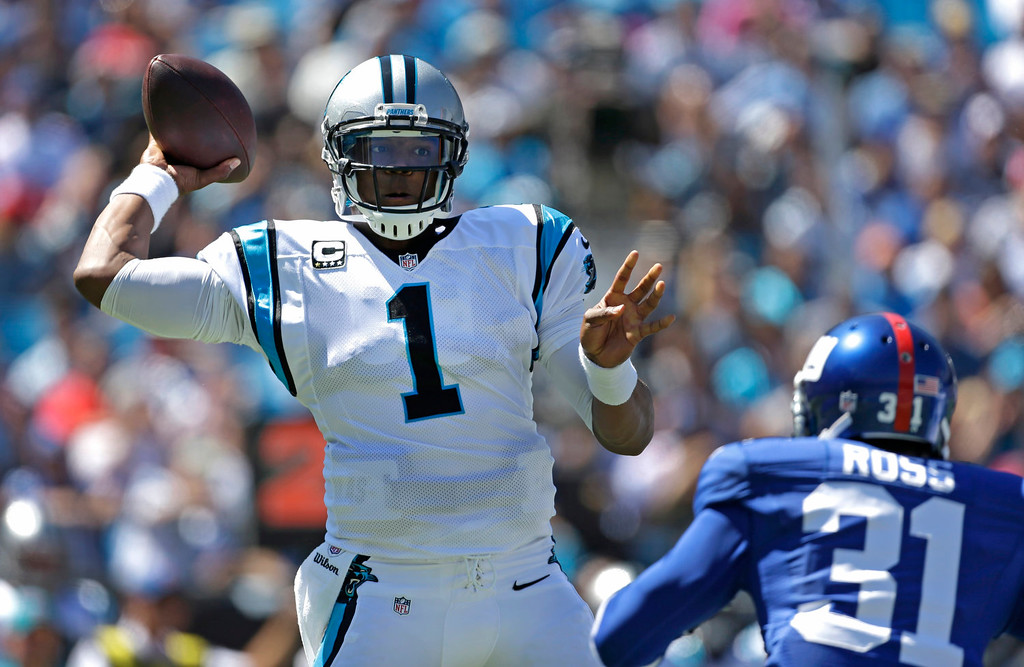 . Carolina Panthers quarterback Cam Newton (1) throws a pass under pressure from New York Giants cornerback Aaron Ross (31) during the first half of an NFL football game in Charlotte, N.C., Sunday, Sept. 22, 2013. (AP Photo/Bob Leverone)