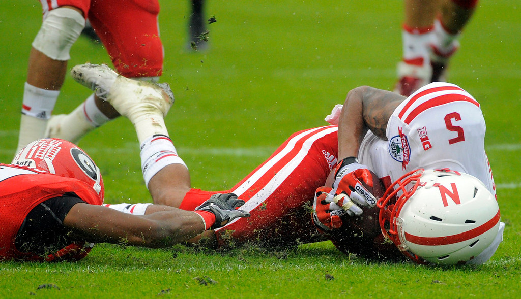 . Nebraska cornerback Josh Mitchell (5) recovers a fumbled kick return by Georgia\'s Reggie Davis during the first half of the Gator Bowl NCAA college football game, Wednesday, Jan. 1, 2014, in Jacksonville, Fla. (AP Photo/Stephen B. Morton)