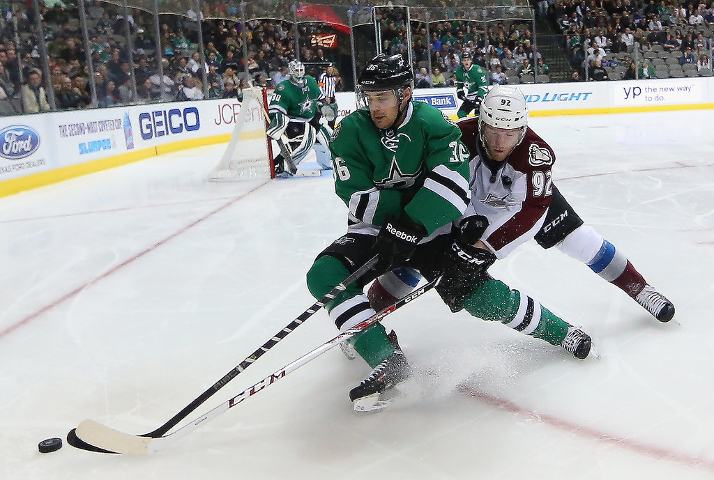 . Cameron Gaunce #32 of the Dallas Stars skates the puck against Gabriel Landeskog #92 of the Colorado Avalanche at American Airlines Center on December 17, 2013 in Dallas, Texas.  (Photo by Ronald Martinez/Getty Images)