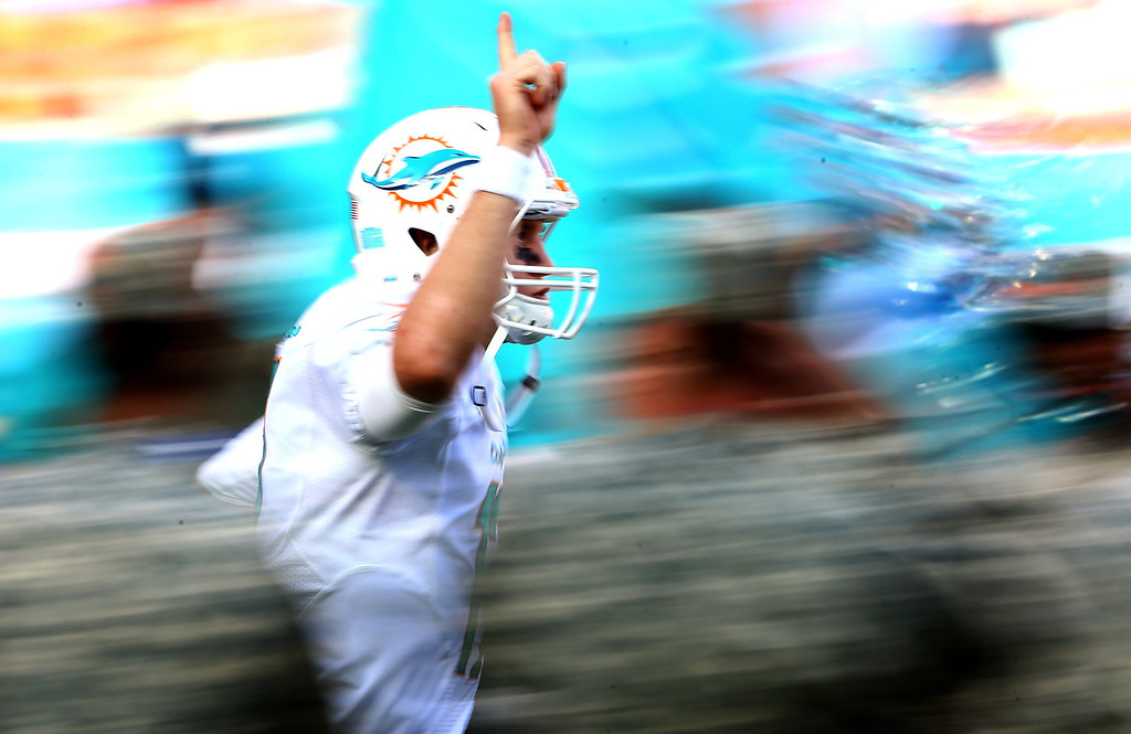 . Ryan Tannehill #17 of the Miami Dolphins runs onto the field for introductions before their game against the San Diego Chargers at Sun Life Stadium on November 17, 2013 in Miami Gardens, Florida.  (Photo by Streeter Lecka/Getty Images)