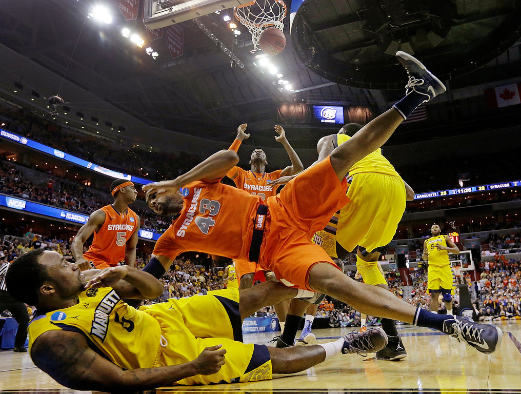 . Syracuse forward James Southerland (43) lands on Marquette guard Junior Cadougan (5) as Syracuse center Baye Keita (12) looks for the rebound during the second half of the East Regional final in the NCAA men\'s college basketball tournament, Saturday, March 30, 2013, in Washington. (AP Photo/Pablo Martinez Monsivais)