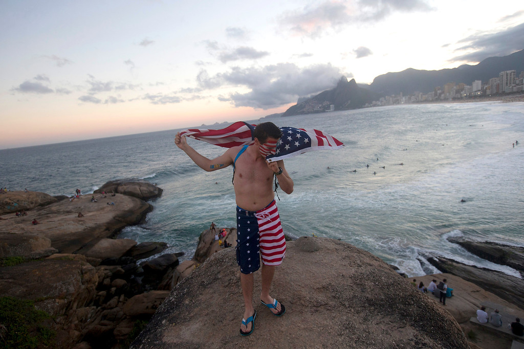 . U.S. fan kisses his national flag at the Arpoador beach before the group G World Cup match between United States and Portugal, in Rio de Janeiro, Brazil, Sunday, June 22, 2014. (AP Photo/Silvia Izquierdo)