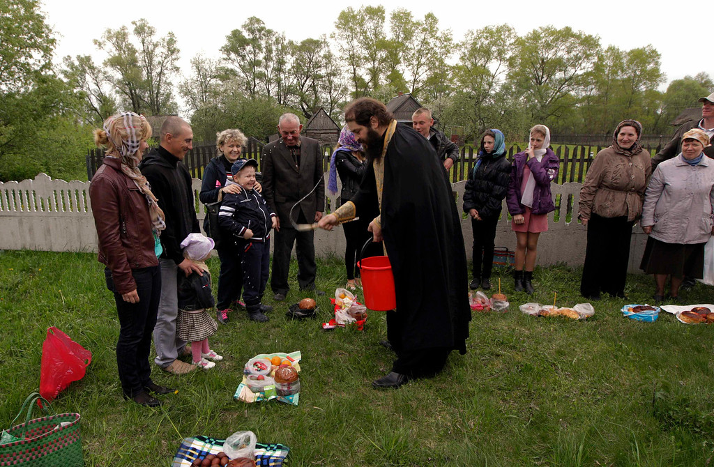 . An Orthodox priest blesses Easter cakes on the eve of Orthodox Easter in the village of Pogost, some 250 km (155 miles) south of Minsk, May 4, 2013. Orthodox Christians mark Easter on Sunday.  REUTERS/Vasily Fedosenko