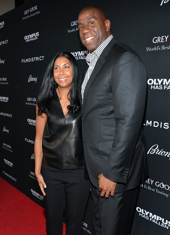 """. Earlitha Kelly (L) and Magic Johnson arrive at the premiere of FilmDistrict\'s \""""Olympus Has Fallen\"""" at ArcLight Cinemas Cinerama Dome on March 18, 2013 in Hollywood, California.  (Photo by Alberto E. Rodriguez/Getty Images)"""