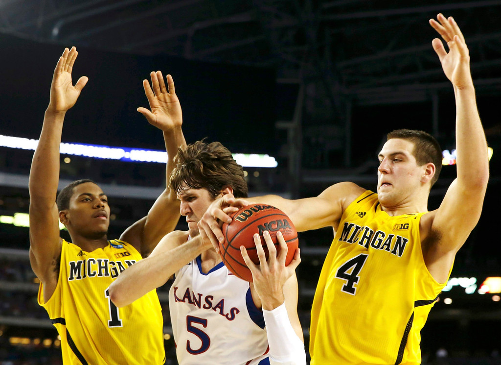 . Kansas Jayhawks center Jeff Withey (C) fights for the ball with Michigan Wolverines forward Glenn Robinson III (L) and forward Mitch McGary (R) during the second half in their South Regional NCAA men\'s basketball game in Arlington, Texas March 29, 2013. REUTERS/Jim Young