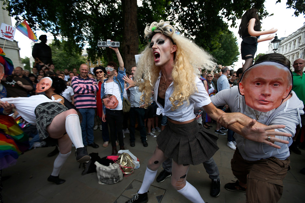""". Activists stage a theatrical play where gays are prevented by others wearing masks depicting Russian President Vladimir Putin, during a protest against Russia\'s new law on gays, in central London, Saturday, Aug. 10, 2013.  Hundreds of protesters called for the Winter 2014 Olympic Games to be taken away from Sochi, Russia, because of a new Russian law that bans \""""propaganda of nontraditional sexual relations\"""" and imposes fines on those holding gay pride rallies. (AP Photo/Lefteris Pitarakis)"""