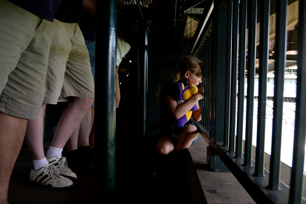 . Sophia Shaw holds her Dinger doll as she peers into the Rockies\' bullpen with her father (not pictured) before the action started at Coors Field. Major League Baseball action between the Colorado Rockies and the Washington Nationals on Monday, July 21, 2014. (Photo by AAron Ontiveroz/The Denver Post)