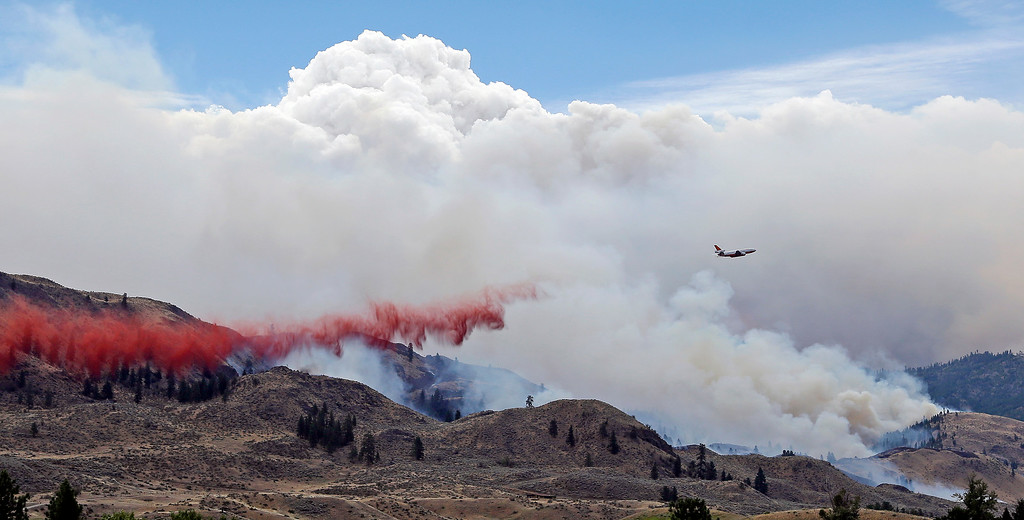 . A DC-10 air tanker drops fire retardant over a wildfire as smoke rises and billows behind Saturday, July 19, 2014, near Carlton, Wash. A wind-driven, lightning-caused wildfire racing through rural north-central Washington destroyed about 100 homes Thursday and Friday, leaving behind solitary brick chimneys and burned-out automobiles as it blackened hundreds of square miles in the scenic Methow Valley northeast of Seattle. (AP Photo/Elaine Thompson)