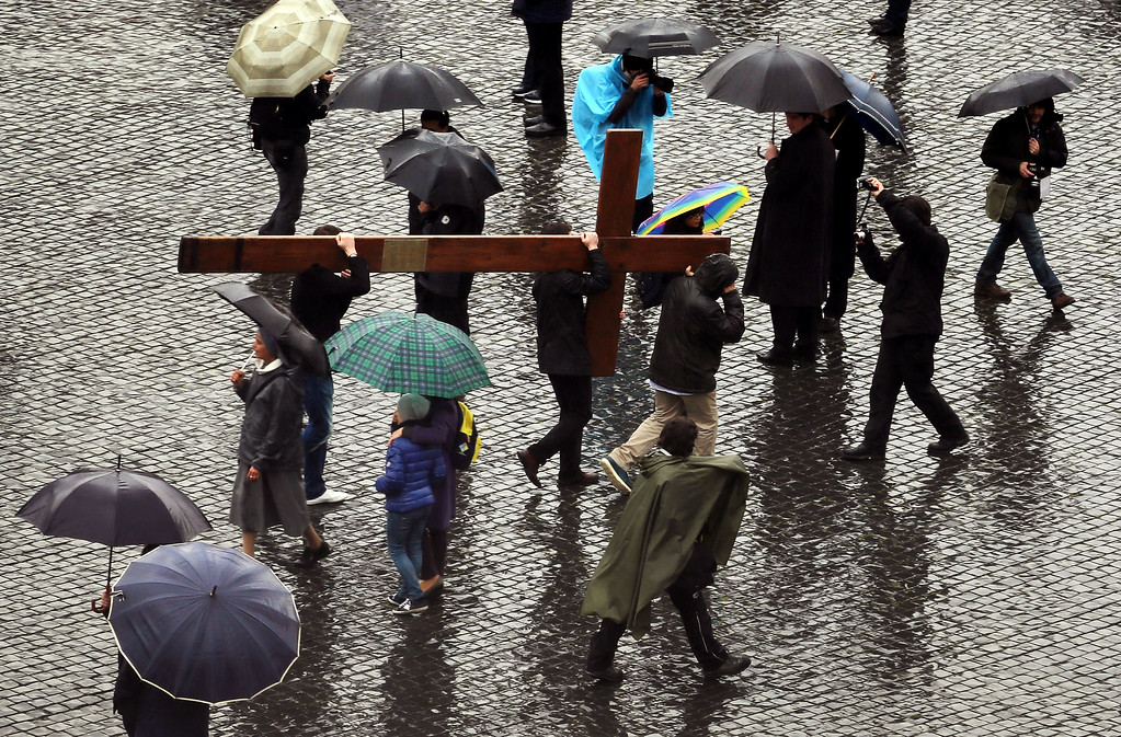 . People carry a cross through St Peter\'s Square as they wait for news on the election of a new Pope on March 13, 2013 in Vatican City, Vatican. (Photo by Joe Raedle/Getty Images)