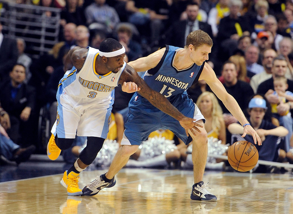 . Denver Nuggets guard Ty Lawson, left, defends against Minnesota Timberwolves guard Luke Ridnour, right, in the second half of an NBA basketball game on Saturday, March 9, 2013, in Denver. (AP Photo/Chris Schneider)